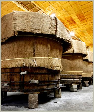 菰(こも)に包まれた30石の大木桶の並ぶ蔵風景